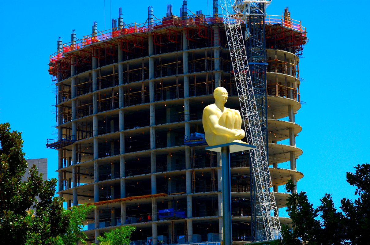 A pole-sitting sculpture in front of a new Condo Tower going up.