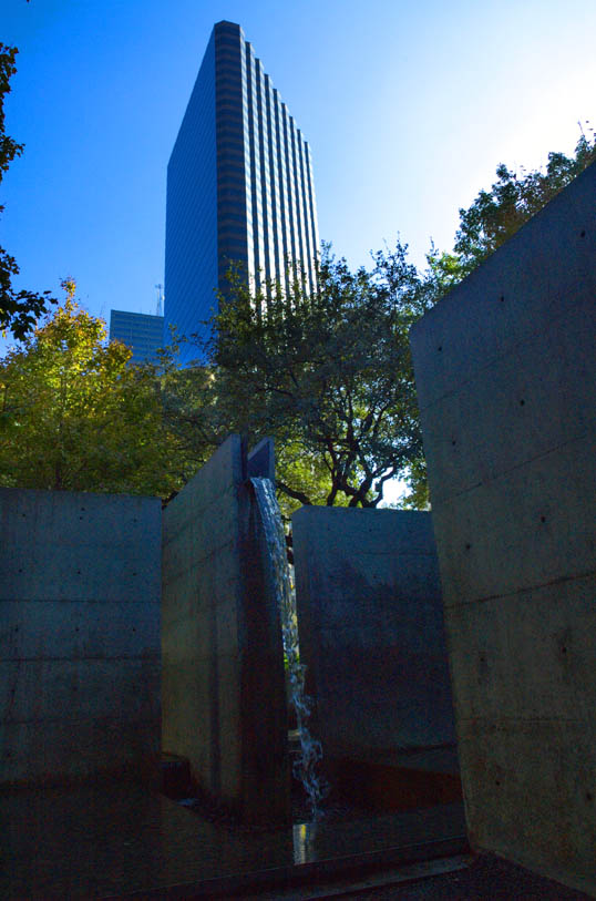 A skyscraper towers over the water feature in Beck Park