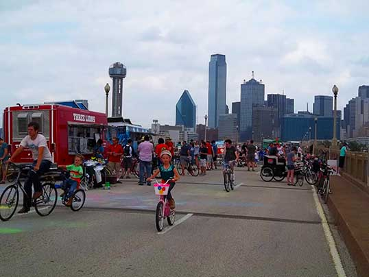 The crowd at Ciclovia Dallas on the Houston Street Viaduct with the Dallas downtown skyline