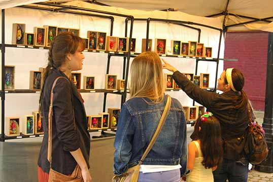 Customers at the Deep Ellum Art Festival looking over David Pound's inventory of little monster heads in boxes.