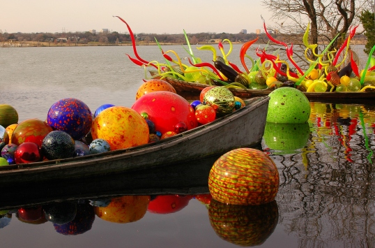 Chihuly Boats full of glass at the Dallas Arboretum. White Rock Lake in the background.
