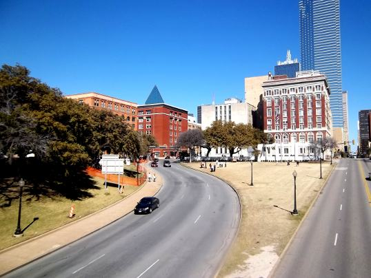 The view a little to the left of Main Street. That's the curve of Elm Street. The grassy knoll is on the left, the Texas Schoolbook Depository is the lighter brick building over the trees. The assassination site is right in front of the two cars coming down the road.