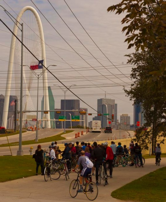 Bike tour stopping to look at a mural by JMR. The Margaret Hunt Hill Bridge and Downtown Dallas in the background.