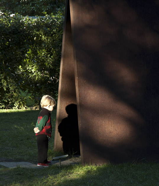 Boy looking at his shadow on Richard Serra's My Curves Are Not Mad - Nasher Sculpture Center, Dallas, Texas