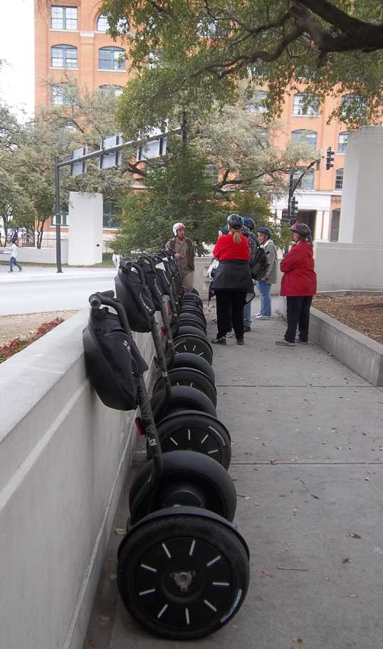 Segways lined up at Dealey Plaza. The Texas School Book Depository in the background.