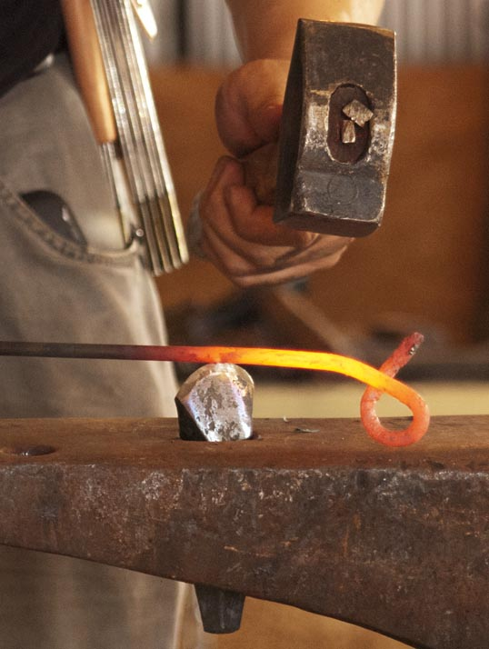 Hammering a heated knot.