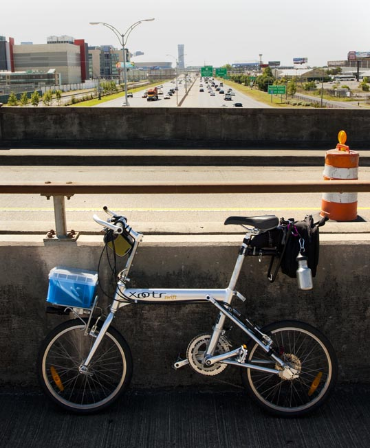 My Xootr Swift folding bike on the bike route over Interstate 10 in New Orleans. Downtown and the Superdome are in the background.