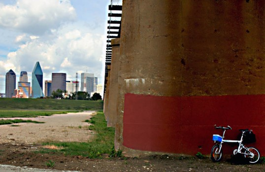 My Xootr Swift folding bicycle leaning against a railroad trestle in the Trinity River Bottoms, Dallas, Texas