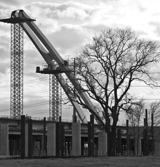 The arches of a second Calatrava designed bridge rise in the river bottoms. The Horseshoe, Dallas, Texas