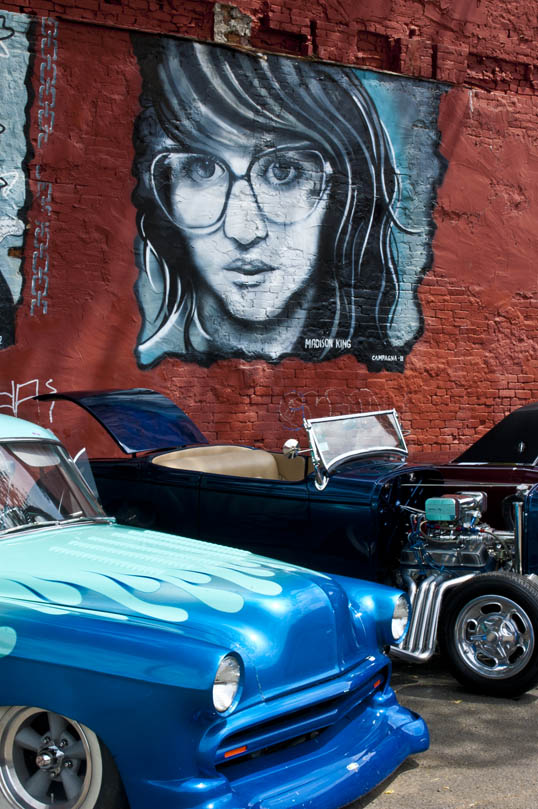 Mural of Madison King behind cars from the Invasion Car Show Deep Ellum Dallas, Texas